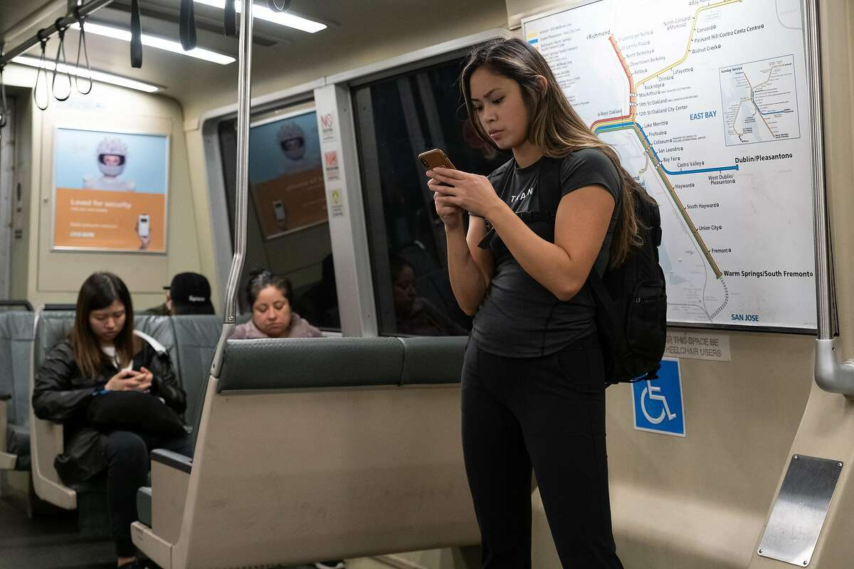 Passengers use phones while traveling on BART toward West Oakland in San Francisco, Calif. on Tuesday, January 7, 2020.