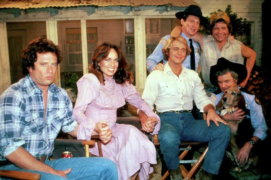 """From left, Lucas K. """"Luke"""" Duke (Tom Wopat) Daisy Duke (Catherine Bach) and Beauregard """"Bo"""" Duke (John Schneider) and others during filming of the last episode of """"The Dukes of Hazzard"""" at CBS Studious, Los Angeles, in 1985. Photo: Paul Harris / Getty Images / Paul Harris Photography"""