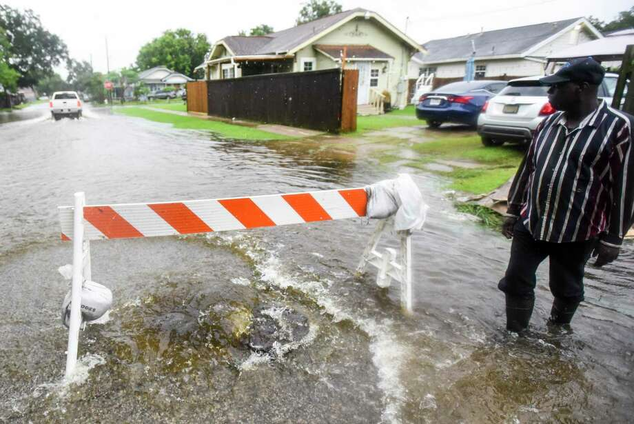 Eddie Davis, whole lives on the block, watches as a truck drives through water on the street while a manhole gushes water out of it on 11th Ave in between 8th Street and 7th Street in Port Arthur Wednesday afternoon. Photo taken on Wednesday, 09/18/19. Ryan Welch/The Enterprise Photo: Ryan Welch, Beaumont Enterprise / The Enterprise / © 2019 Beaumont Enterprise