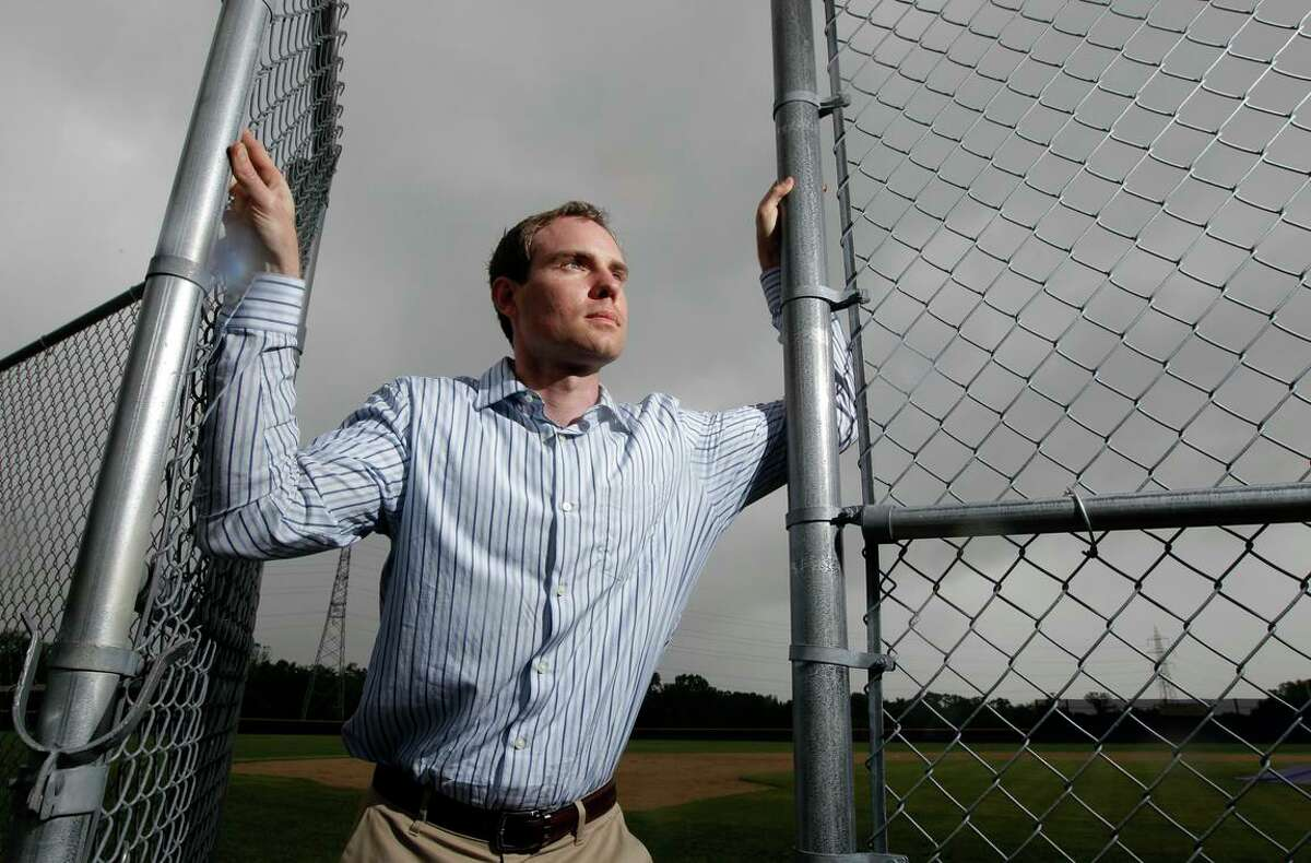FILE - In this May 23, 2013, photo, Garrett Broshuis poses for a photo at a baseball field in St. Louis. Broshuis is the driving force of a lawsuit against Major League Baseball, alleging violations of federal wage and overtime laws in a case some legal observers suggest has significant merit. (AP Photo/Jeff Roberson, File)