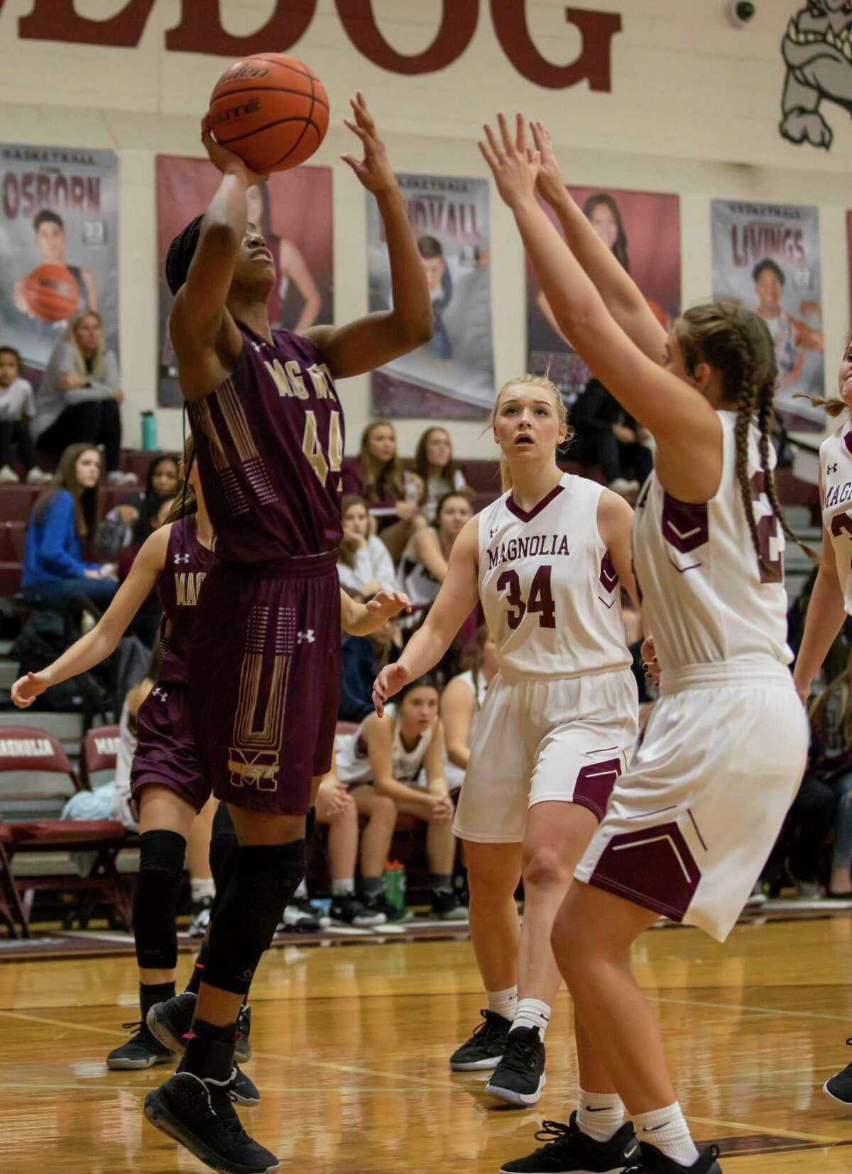 Magnolia West forward Kamryn Jones (44) shoots for the basket through Magnolia guard Audrey Andrews (23) and Magnolia point forward Sophie Christiansen (34) in a District 19-5A girls basketball game in Magnolia on Tuesday, Jan. 7, 2020.