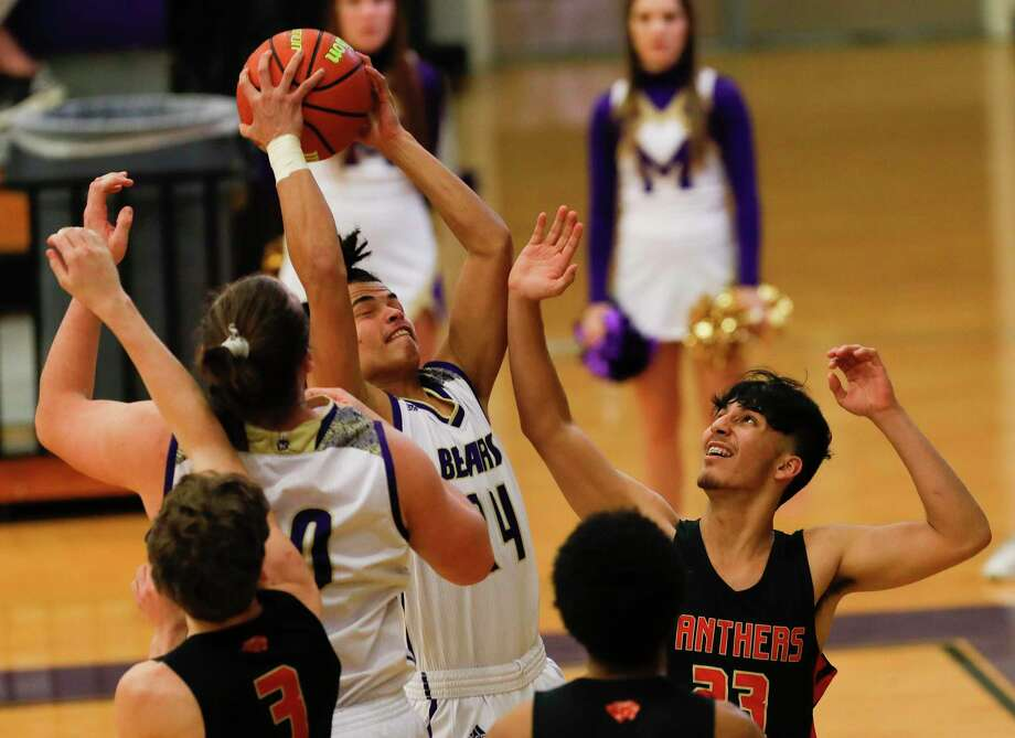 Montgomery forward Isaac Lawson (24) grabs a rebound over Caney Creek forward Sal Loduca (23) during Bears' win at Montgomery High School on Tuesday Photo: Jason Fochtman, Houston Chronicle / Staff Photographer / Houston Chronicle © 2020