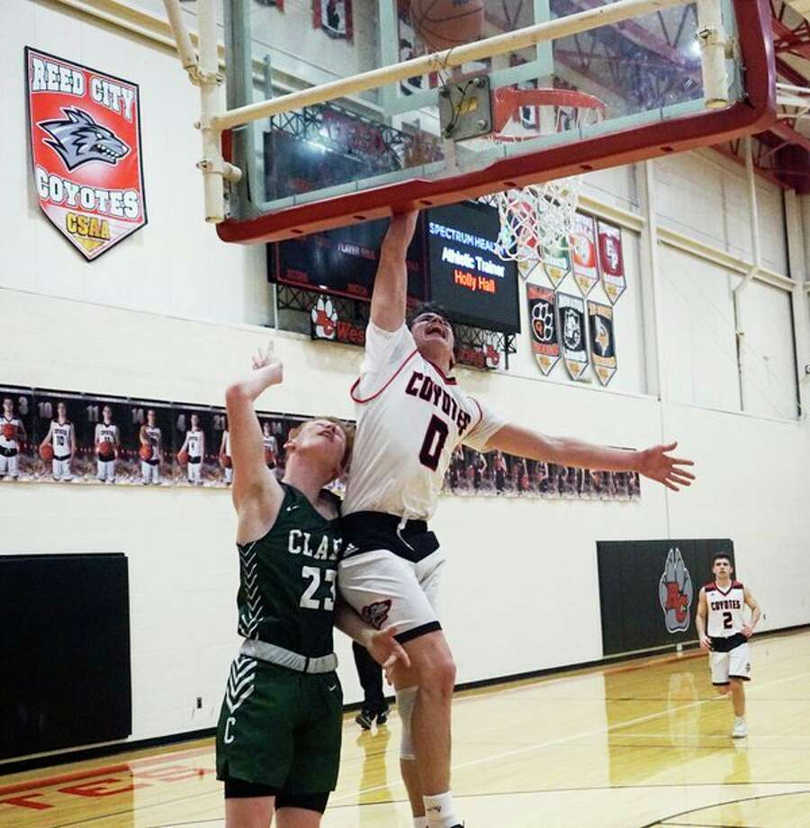 Reed City's Landen Tomaski blocks a lay-up attempt by Clare's Todd Lake during RC's 54-36 home defeat on Tuesday night. (Pioneer photo/Joe Judd)