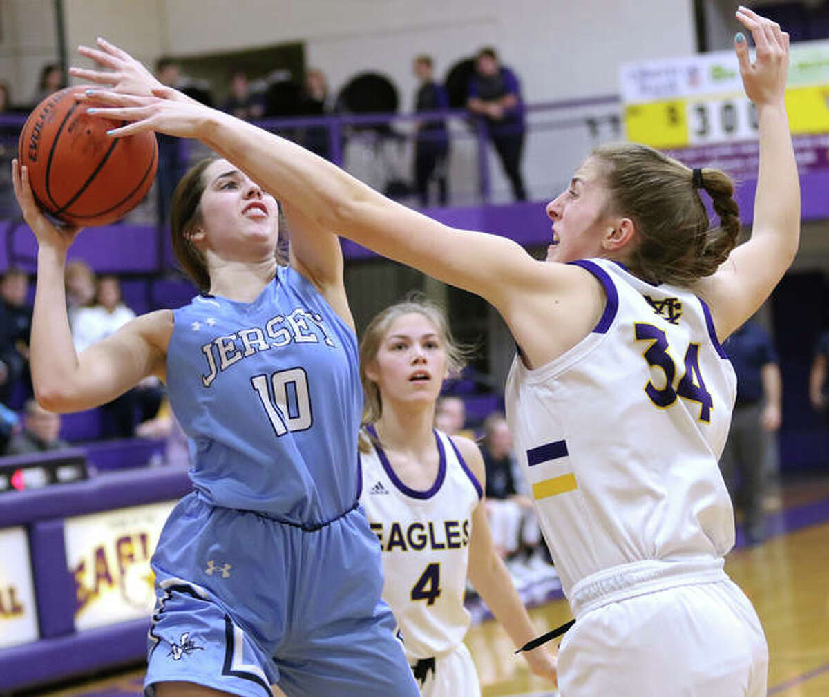 Jersey's Abby Manns (10) tries to shoot over Civic Memorial's Jackie Woelfel (right) while the Eagles' Maura Niemeier (4) watches the play in a Mississippi Valley Conference girls basketball game Tuesday night in Bethalto.