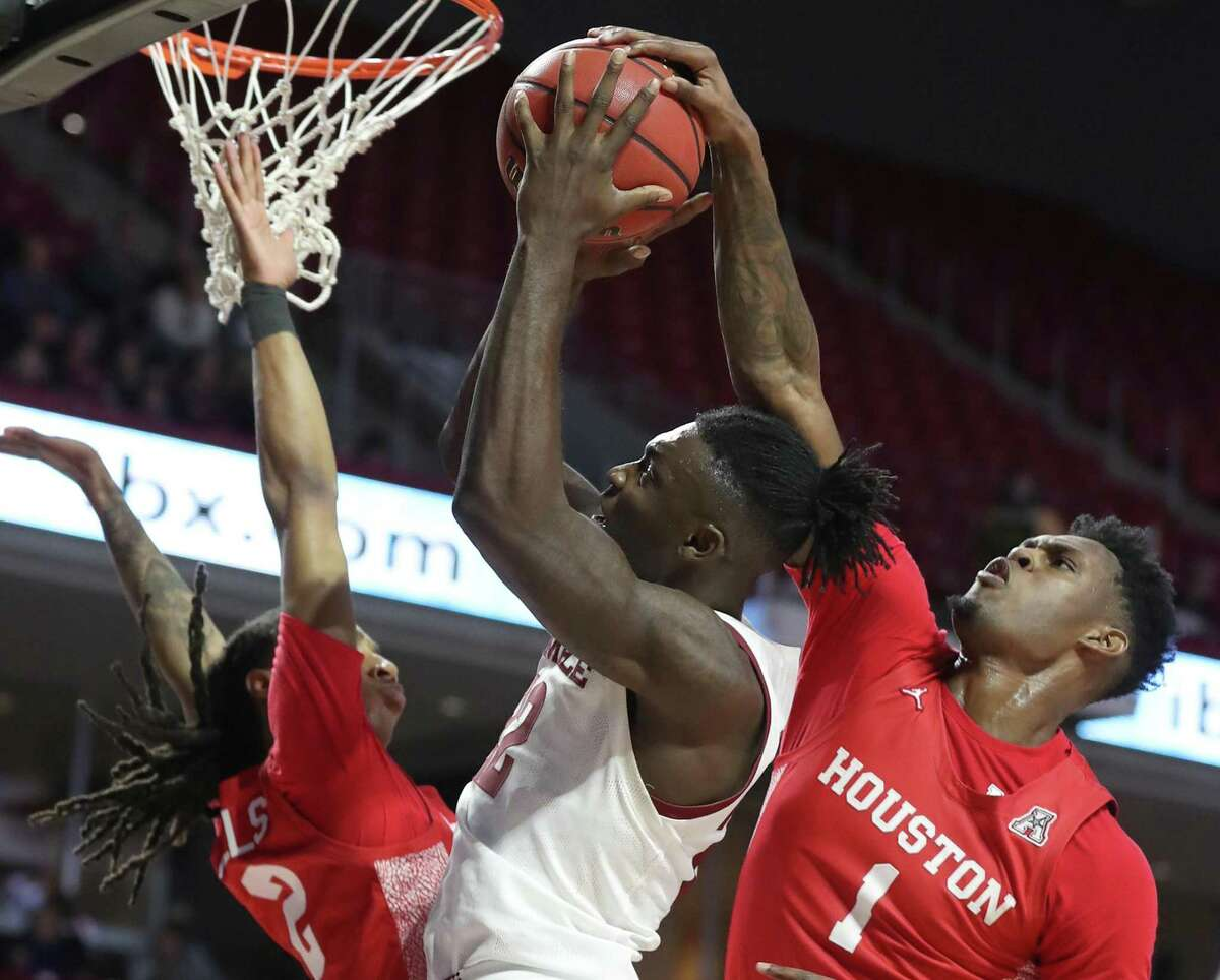 De'Vondre Perry, center, of Temple has his shot blocked by Chris Harris, right, of Houston during the 2nd half at the Liacouras Center on Jan 7, 2020. Caleb Mills is left.