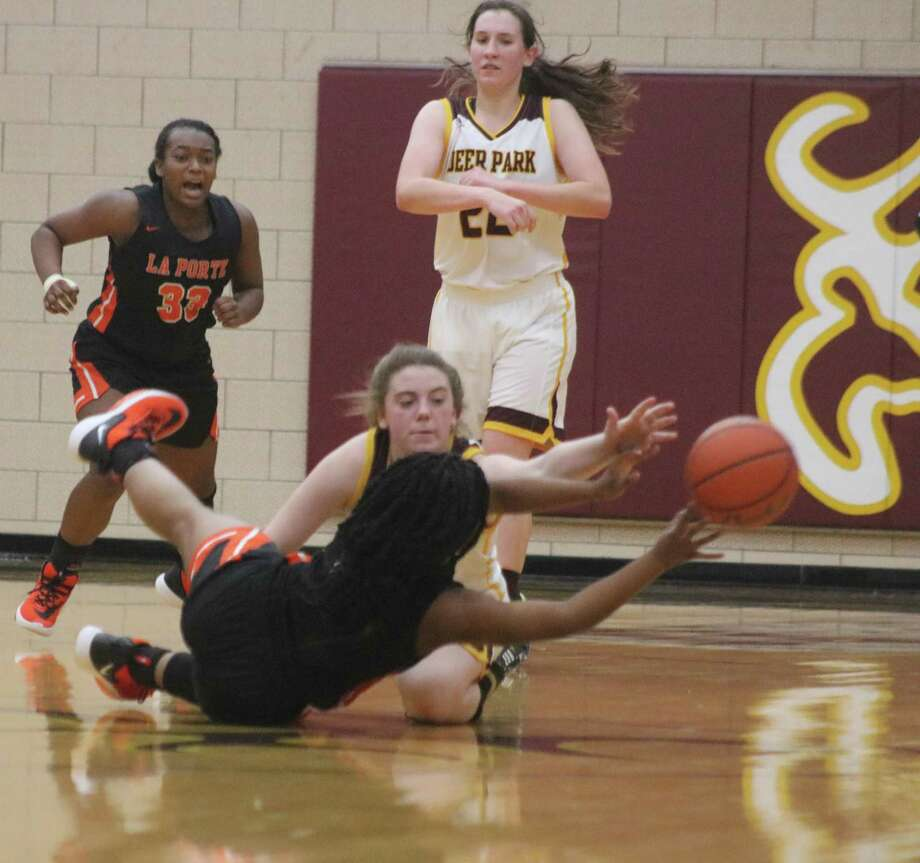 In an awkward position, La Porte's Koko Wooley manages to dump the ball off as Deer Park's Jennah Savage attempts to stop her during second-half action Tuesday night.. Photo: Robert Avery