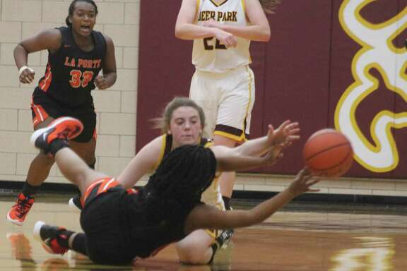In an awkward position, La Porte's Koko Wooley manages to dump the ball off as Deer Park's Jennah Savage attempts to stop her during second-half action Tuesday night..