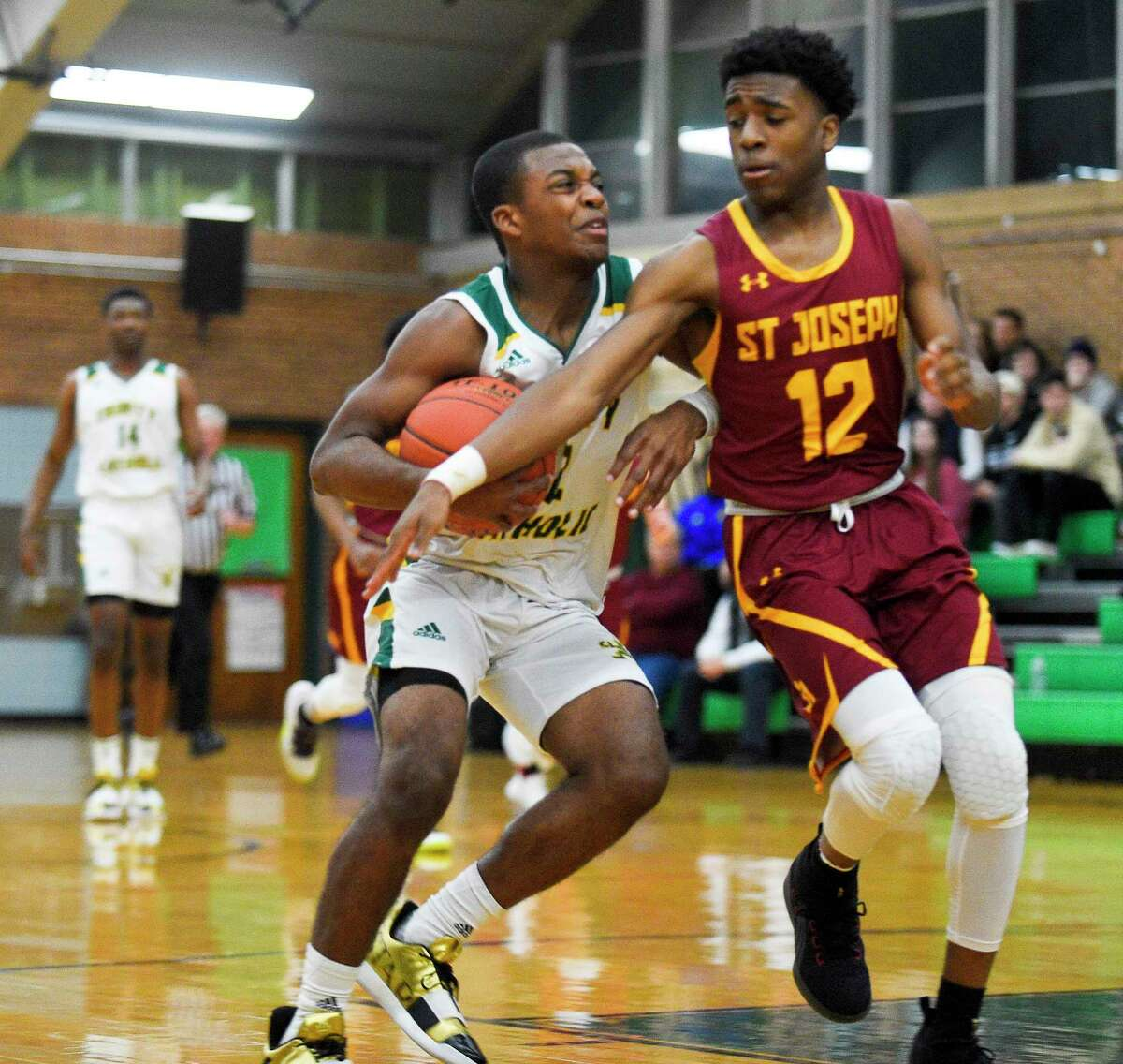 St Joseph Jason James (12) reachs on Trinity Catholic's Branden Louis (12) drive to the basket in a boys basketball game at Walsh Court on Jan. 7, 2020 in Stamford, Connecticut.