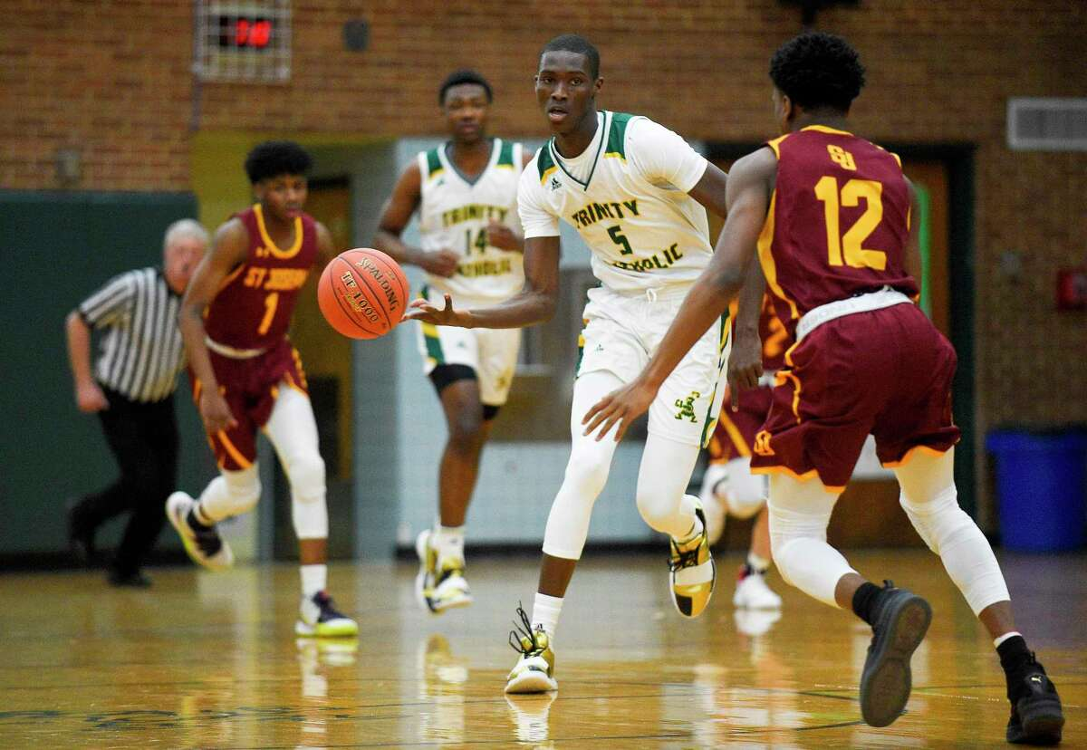 Trinity Catholic forward Abdoul-Rassoul Abakar Hachym (5) passes the ball off on a drive under pressure from St. Joseph gaurd Jason James at Walsh Court on Tuesday in Stamford.