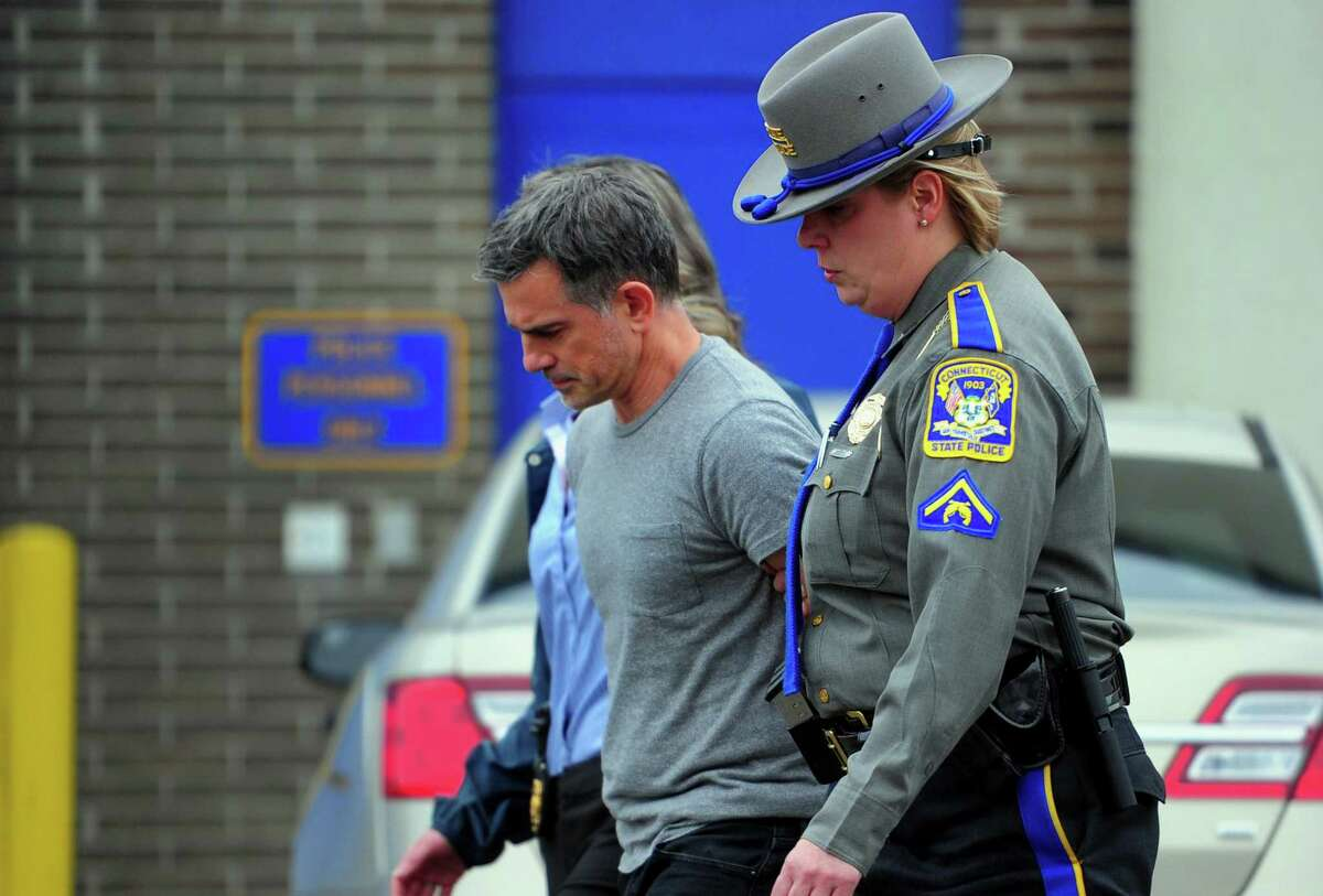 Fotis Dulos is escorted to an awating police vehicle after being arrested and processed at State Police Troop G Headquarters in Bridgeport, Conn., on Tuesday Jan. 7, 2020.
