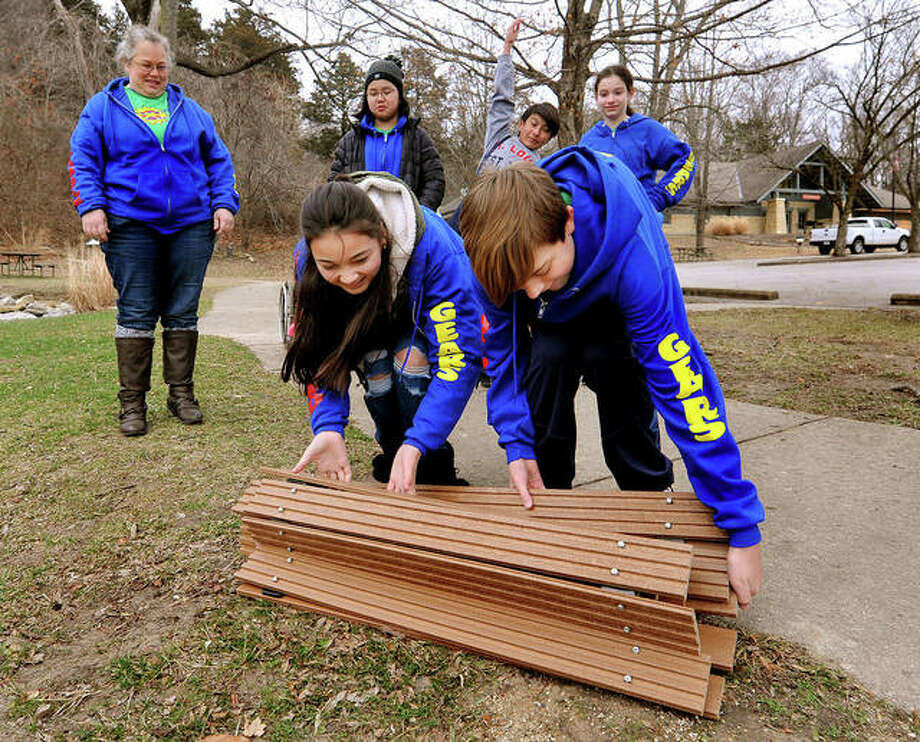 Reanna Compton, 13, left, and Tristan Luehmann, 12, roll out the St. John Neumann Catholic School robotics team's invention, the Passable Path, as their coach and other team members watch at Pere Marquette State Park on Friday in Grafton. The robotics team, Scrambled Gears, was demonstrating how their path could eliminate mobility barriers that prevent wheelchairs from going over uneven surfaces. Photo: Photos By Thomas Turney|The Intelligencer