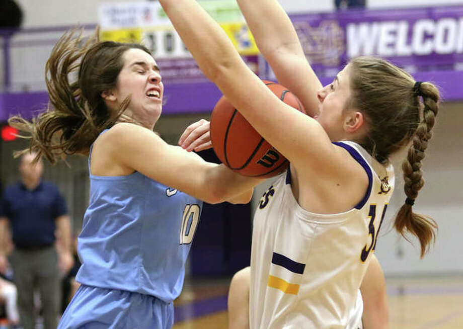 Jersey's Abby Manns (left) looses control of the basketball while going up for a shot over CM's Jackie Woelfel in the first quarter Tuesday night in a Mississippi Valley Conference girls basketball game in Bethalto. Photo: Greg Shashack / The Telegraph