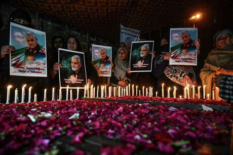 Shiite Muslims hold pictures of slain top Iranian general Qasem Soleimani to pay him tribute during a candle light vigil in Islamabad Jan. 8, 2020. Iran fired a volley of missiles late on Jan. 7 at Iraqi bases housing U.S. and foreign troops in Iraq, the Islamic republic's first act in its promised revenge for the U.S. killing of a top Iranian general.