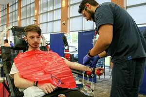 Sal Castaneda, right, with South Texas Blood and Tissue Center, prepares Jacob Scroggins, 17, for a blood donation during a blood drive on April 12, 2019.