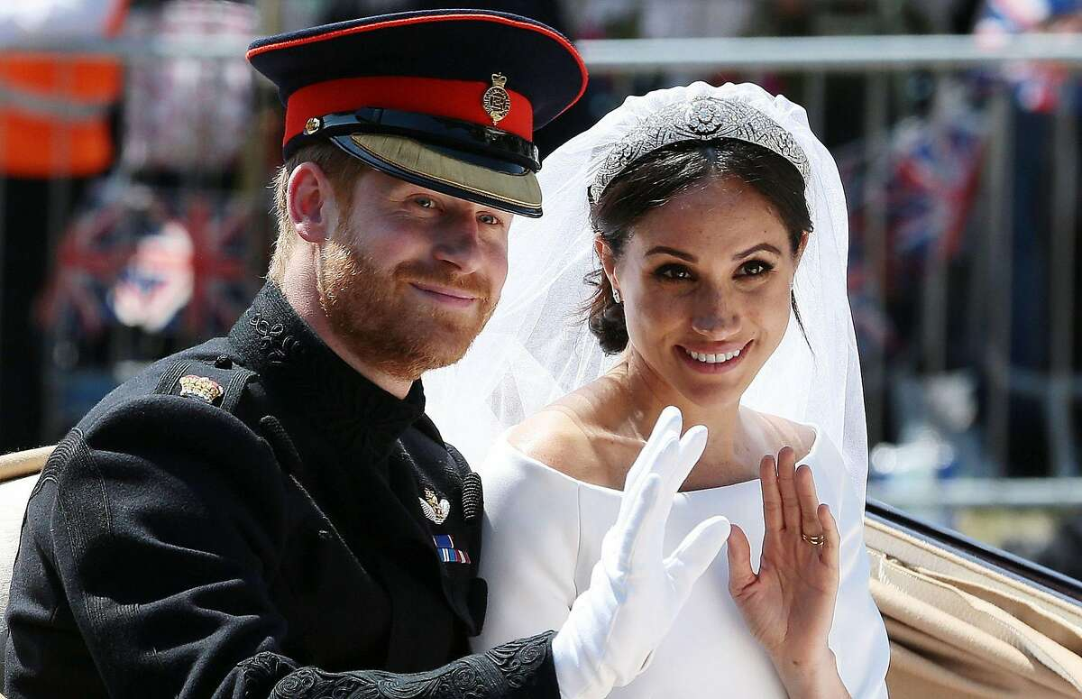 (FILES) In this file photo taken on May 19, 2018 Britain's Prince Harry, Duke of Sussex and his wife Meghan, Duchess of Sussex wave from the Ascot Landau Carriage during their carriage procession on the Long Walk as they head back towards Windsor Castle in Windsor, oafter their wedding ceremony. - Britain's Prince Harry and his wife Meghan will step back as senior members of the royal family and spend more time in North America, the couple said in a historic statement Wednesday. (Photo by Aaron Chown / POOL / AFP) (Photo by AARON CHOWN/POOL/AFP via Getty Images)