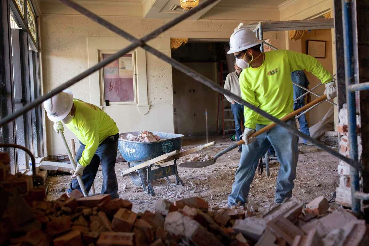 """Two construction workers begin to remove the former concrete flooring of the Crighton Theater in Conroe, Wednesday, Jan. 8, 2020. The Crighton Theater renovation will be an estimated 60 percent complete by their first showing of the year, """"Thoroughly Modern Millie,"""" on Feb. 14, 2020."""
