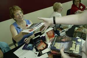 Houston-area romance writer Joanna Wayne hands out an autographed copy of her book during a Romance Writers of America event.