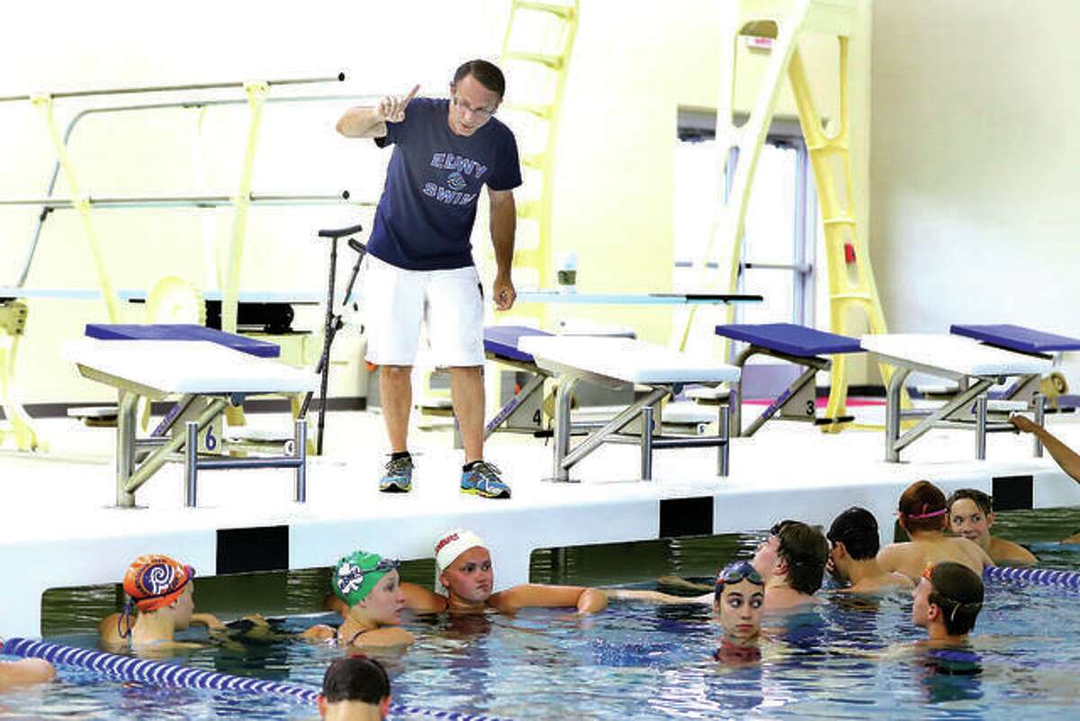 Edwardsville YMCA Breakers swim team coach Bob Rettle addresses some of his swimmers at a practice session in the Chuck fruit Aquatic Center at Edwardsville High School.