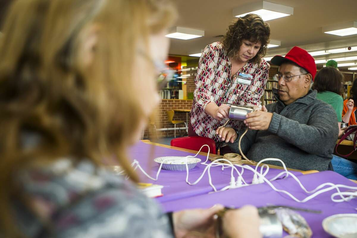 Library employee Alison Bookmyer, center, assists a man identified as Piano Ray, right, as he constructs a bird feeder during a crafting class Wednesday, Jan. 8, 2020 at Grace A. Dow Memorial Library. (Katy Kildee/kkildee@mdn.net)