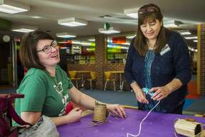 Alisha Hasselhuhn, left, laughs while constructing a bird feeder while library employee Lisa Novak, right, assists her during a crafting class Wednesday, Jan. 8, 2020 at Grace A. Dow Memorial Library. (Katy Kildee/kkildee@mdn.net)