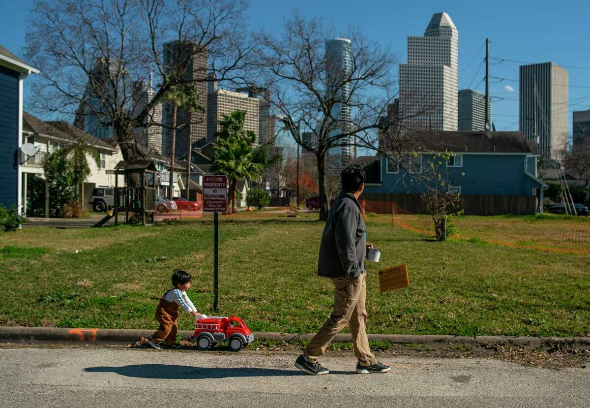 Ben Temcharoen walks with his two-year-old son, Hayden, around their block in the Freedman's Town area of the Fourth Ward just west of downtown Houston, Wednesday, Jan. 8, 2020. Temcharoen bought his 2001-built home in the neighborhood in 2006 and has lived there since, enjoying the ability to walk or bike to work in downtown Houston.