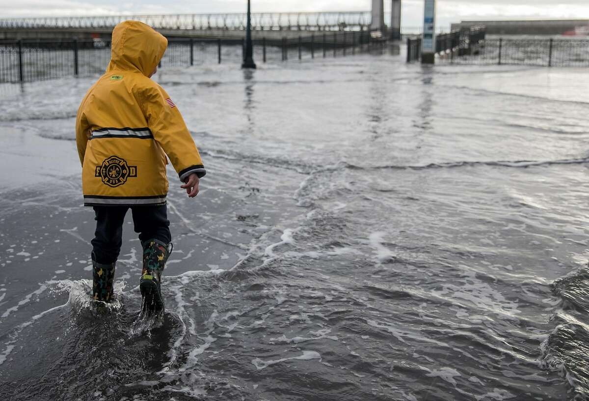 A young boy who wished not to be named plays in the water as large waves crash into Pier 14 along the Embarcadero in San Francisco, Calif. Saturday, Jan. 5, 2019 as a winter storm moves through the Bay Area.