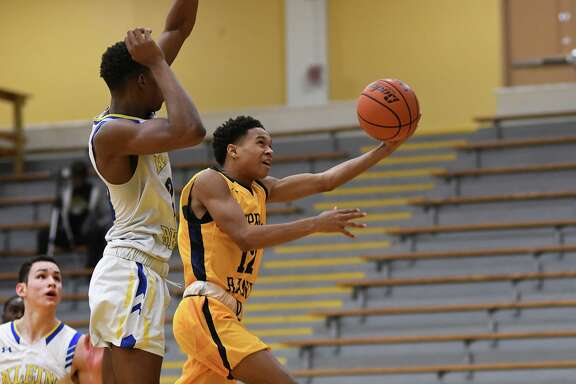 Cy Ranch sophomore Mike Hawkins (12) drives to the hoop against Klein junior Thirhrey Smiley, left, during their opening round matchup at the 55th Annual Conroe Christmas Classic at Conroe High School on Dec. 27, 2019.
