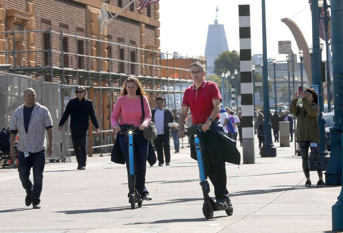 Commuters using Skip scooters next to the Ferry building on the Embarcadero on Monday, Oct. 14, 2019, in San Francisco, Calif.