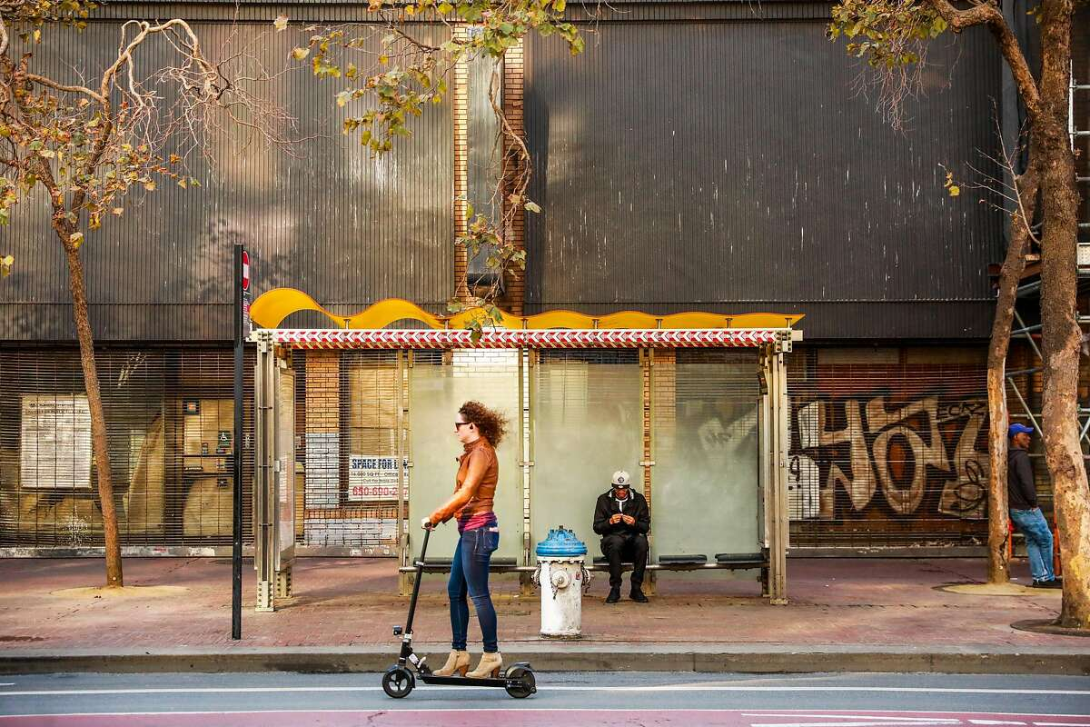 A woman rides a scooter down Market Street in San Francisco, California, on Monday, Oct. 7, 2019.