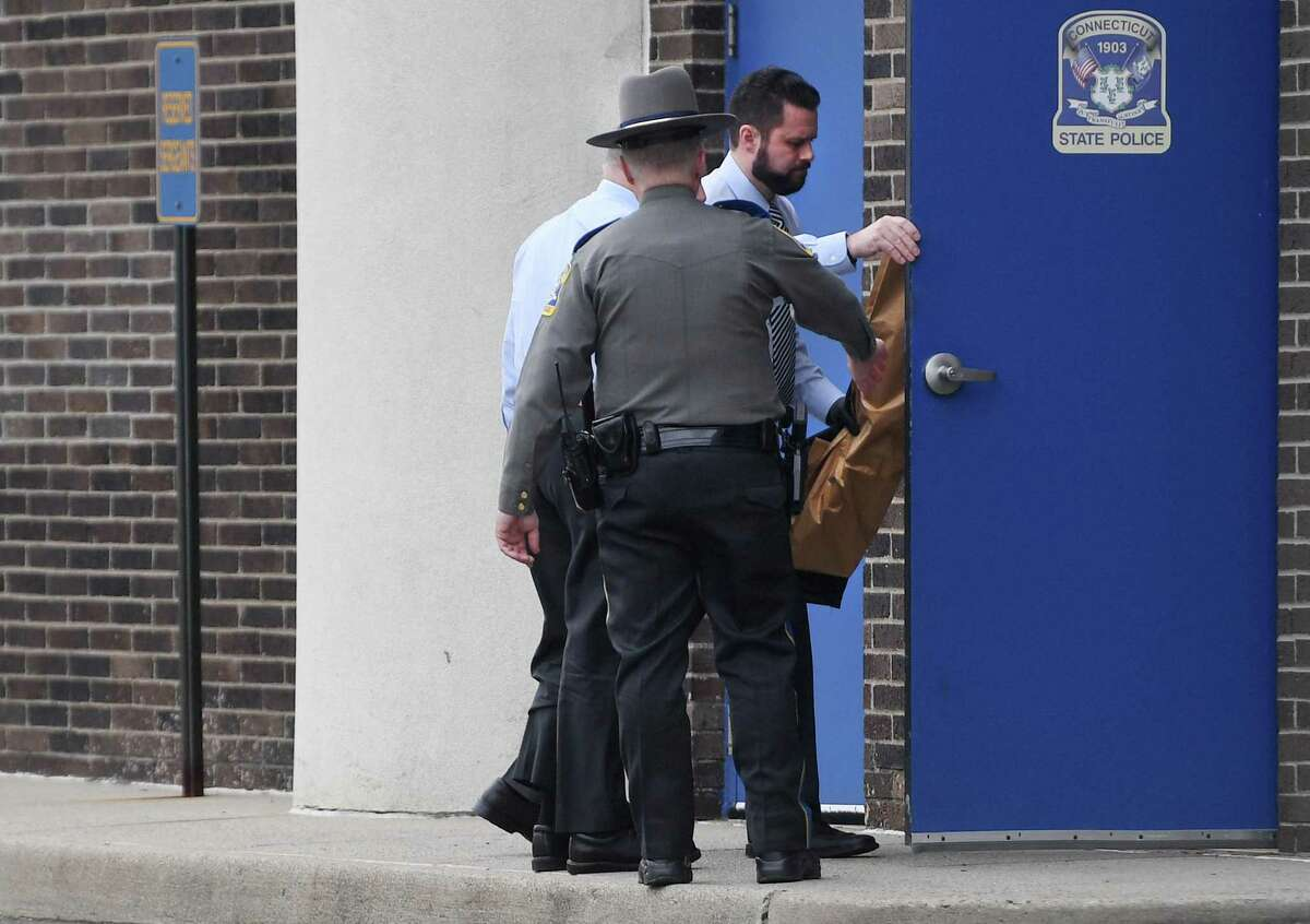 State Police carry a bag into State Police Troop G in Bridgeport, Conn. following the arrest of Fotis Dulos on murder charges on Tuesday, January 07, 2020. It's unclear what is in the bag.