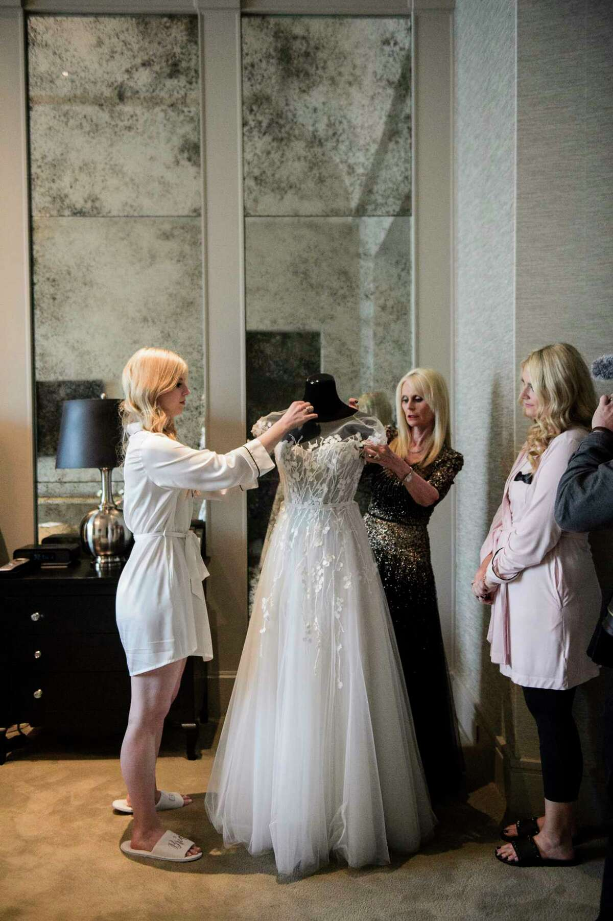 Jo Lynn Falgout helps daughter Kimberly Falgout Scheele dress in her wedding gown from Joan Pillow Bridal Salon.