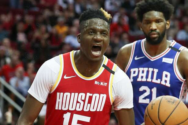 Houston Rockets center Clint Capela (15) celebrates after dunking under pressure of Philadelphia 76ers center Joel Embiid (21) during the 2nd half of an NBA basketball game at Toyota Center on Friday, Jan. 3, 2020, in Houston.