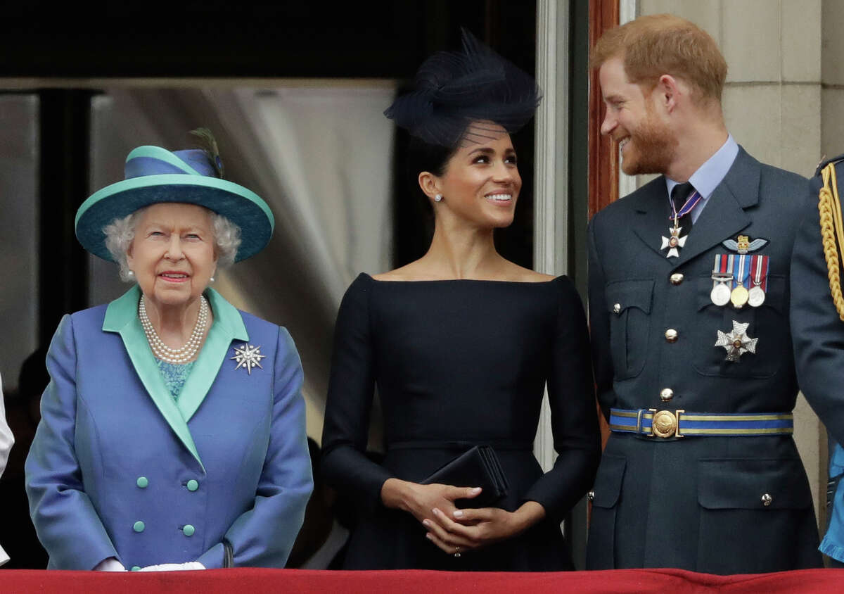 FILE - In this Tuesday, July 10, 2018 file photo Britain's Queen Elizabeth II, and Meghan the Duchess of Sussex and Prince Harry watch a flypast of Royal Air Force aircraft pass over Buckingham Palace in London. In a stunning declaration, Britain's Prince Harry and his wife, Meghan, said they are planning