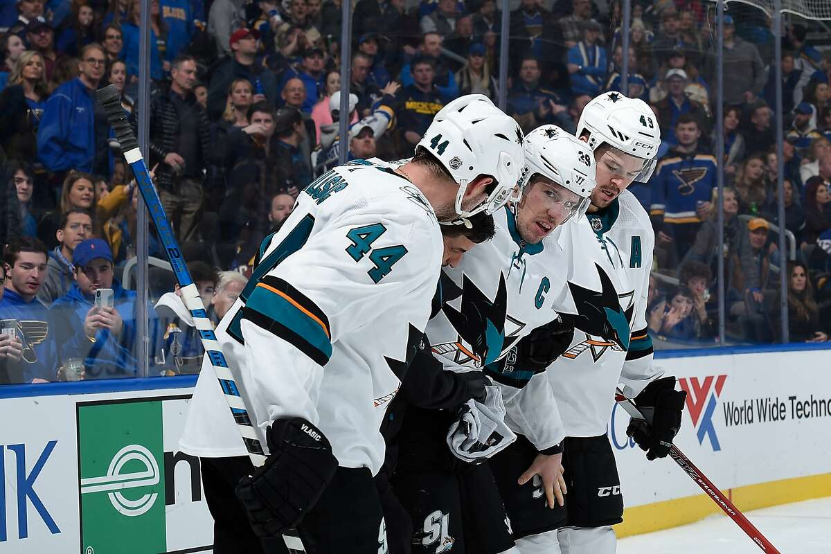 ST. LOUIS, MO - JANUARY 7: Logan Couture #39 of the San Jose Sharks is helped off the ice by teammates and a trainer after sustaining an injury against the St. Louis Blues at Enterprise Center on January 7, 2020 in St. Louis, Missouri. (Photo by Joe Puetz/NHLI via Getty Images)