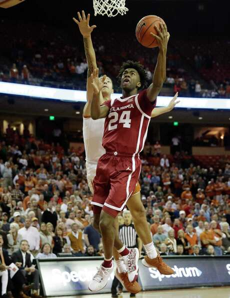 Oklahoma's Jamal Bieniemy scores two of his 11 points past Texas' Kamaka Hepa (33) in the first half on Wednesday.