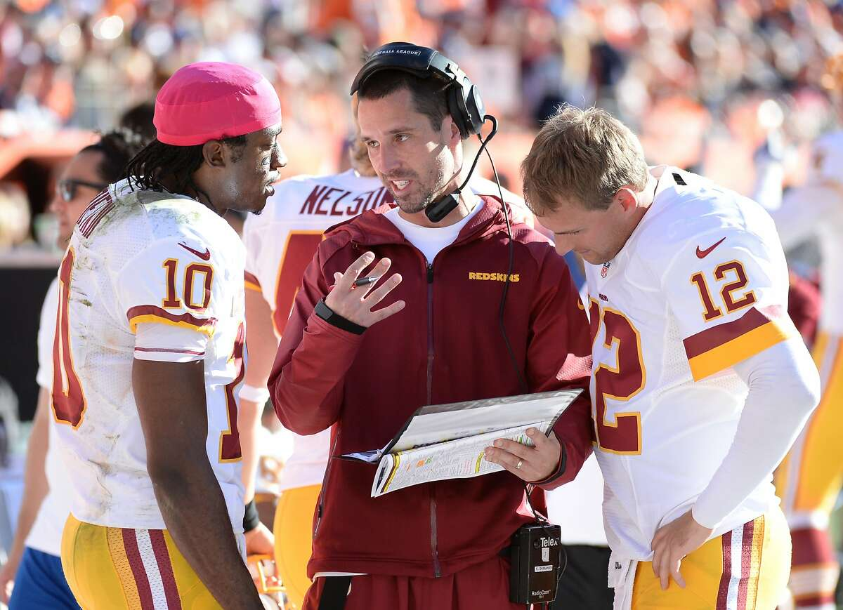 Denver,CO - October 27: Washington Redskins offensive coordinator Kyle Shanahan talks with his QB's Robert Griffin III (10) and Kirk Cousins (12) during second quarter action against the Denver Broncos on October 27, 2013 in Denver, CO. (Photo by Jonathan Newton / The Washington Post via Getty Images)