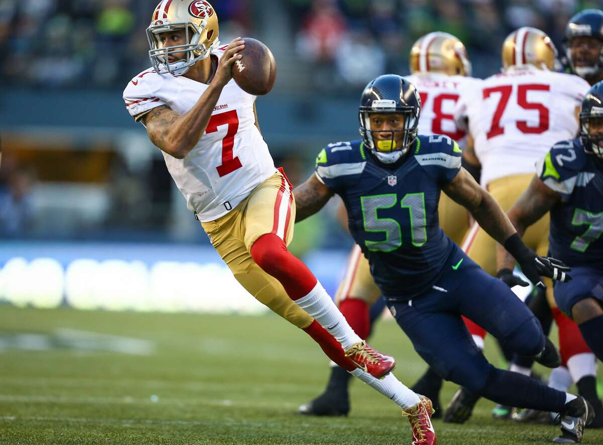 San Francisco 49ers quarterback Colin Kaepernick tries to evade Seattle Seahawks player Bruce Irvin during a game at CenturyLink Field in Seattle. Photographed on Sunday, December 14, 2014. (Joshua Trujillo, seattlepi.com)