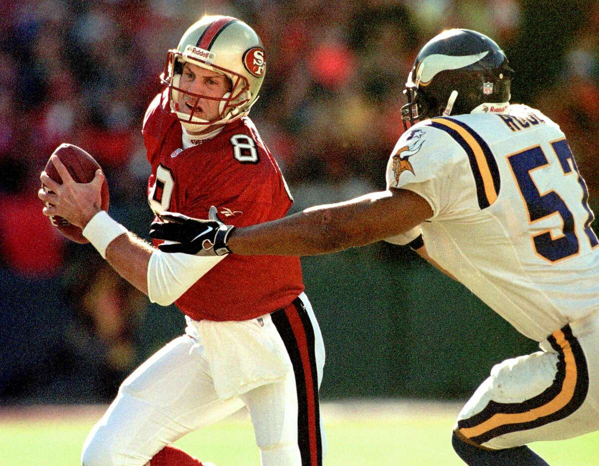 SAN FRANCISCO, CA - JANUARY 3: San Francisco 49ers quarterback Steve Young (L) scrambles away from Minnesota Vikings defender Dwayne Rudd (R) as Young runs for a gain in the first quarter of their NFC playoff game 03 January at Candlestick Park in San Francisco, CA. (Photo credit should read MONICA DAVEY/AFP via Getty Images)