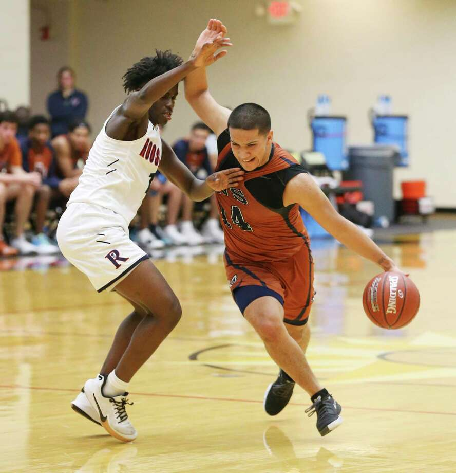 Madison's Christian Vasquez (14) tries to fight off the defense by Roosevelt's Abdikadir Ali (01) during their basketball game at Littleton Gym on Wednesday, Jan. 8, 2020. The Roughriders defeated the Mavericks, 52-48. Photo: Kin Man Hui, San Antonio Express-News / Staff Photographer / **MANDATORY CREDIT FOR PHOTOGRAPHER AND SAN ANTONIO EXPRESS-NEWS/NO SALES/MAGS OUT/ TV OUT