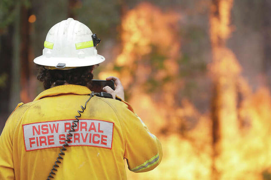 A firefighter uses his phone Wednesday to record a controlled burn near Tomerong, Australia, that was an effort to contain a larger fire nearby. About 2,300 firefighters in New South Wales state were making the most of relatively benign conditions by frantically consolidating containment lines around more than 110 blazes and patrolling for lightning strikes, state Rural Fire Service Commissioner Shane Fitzsimmons said. Photo: Rick Rycroft | AP