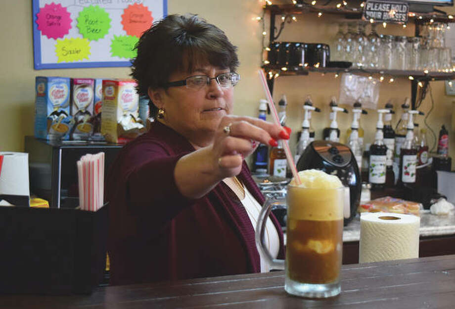 Stacy Pinkerton, owner of A Little Bit of This & That in South Jacksonville, serves a root beer float Wednesday. Pinkerton said the store offers a variety of food and drinks, as well as non-food items such as jewelry and essential oils. Photo: Marco Cartolano | Journal-Courier