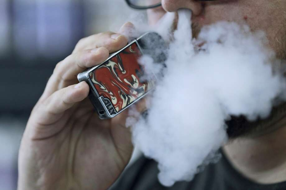 In this file photo, a man using an electronic cigarette exhales. Photo: Associated Press