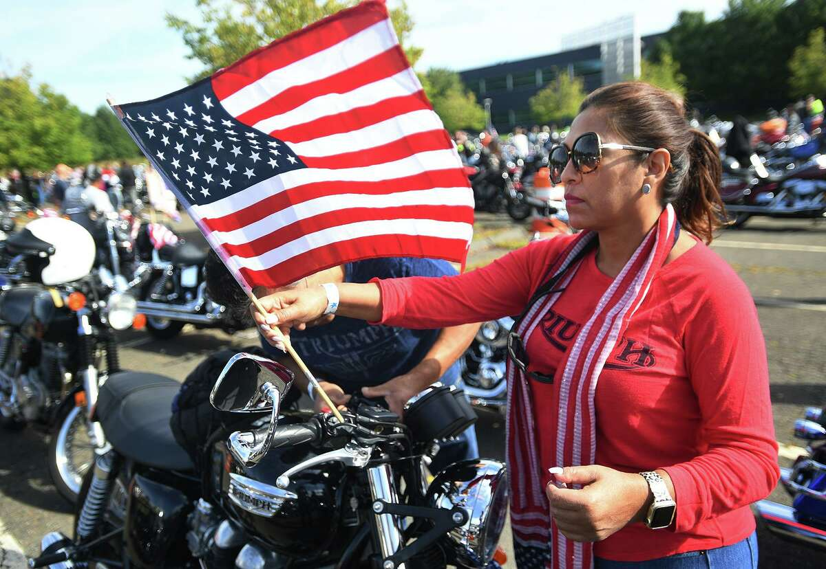Silvia Flores, of Redding, attaches an American flag to the handlebars as she and husband Jose Flores prepare for the start of the annual CT United Ride, Connecticut's largest 9/11 tribute, in Norwalk, Conn. on Sunday, September 8, 2019.