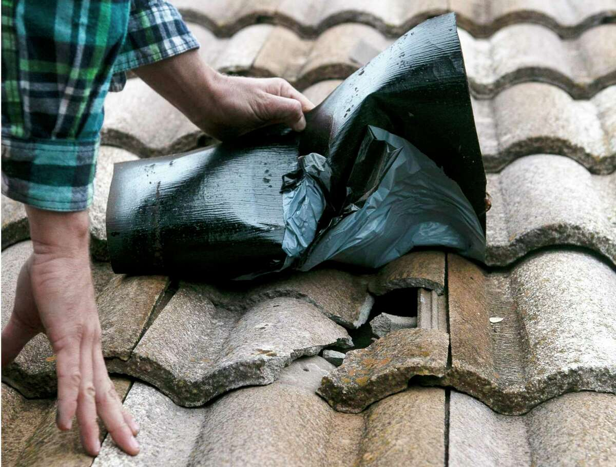 Contractor Corey Hollowich pulls back a patch to expose damaged tiles on the roof of USAA insurance customer Larry Sultenfuss' home in the Dominion in San Antonio, Texas, on Dec. 10, 2019. The neighborhood was hit by a hail storm in April that damaged many homes' roofs. Months later, it's easy to spot the homes insured by USAA, according to homeowners- they're the roofs that are still compromised.