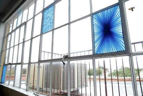 Tony Feher, who worked at Artpace in 2012, left behind three blue tape pieces in the window of the apartment where he stayed.