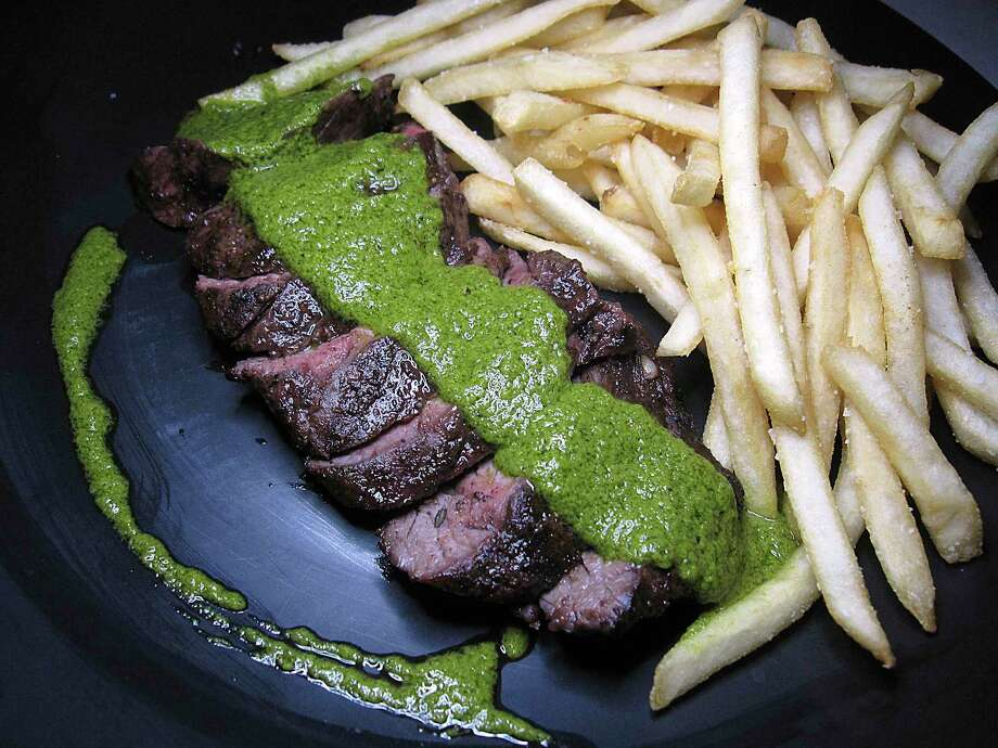 Steak frites comes with chimichurri sauce at Julia's Bistro & Bar. Photo: Mike Sutter /Staff