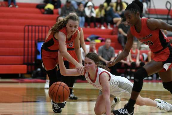 Huffman Hargrave junior Kyleigh Boyd-Smith, center, scrambles for a loose ball against a pair of Huntington defenders on a play late in the second quarter of a game at Hargrave High School on Jan. 7, 2020.