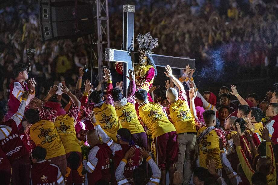 Catholic devotees jostle one another to touch the Black Nazarene during its annual procession in Manila. The procession is attended by as many as 4 million barefoot believers. Photo: Ezra Acayan / Getty Images