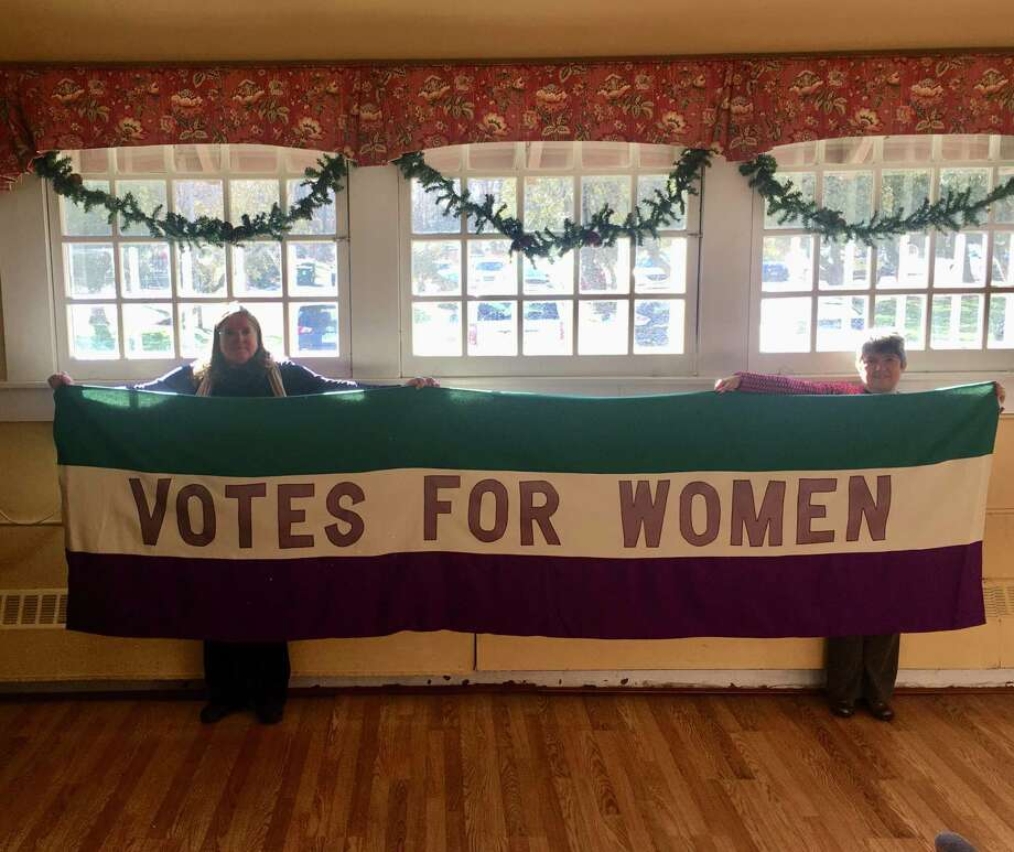 "Marilyn Carroll, president of League of Women Voters of Ridgefield, left, and Rev. Maria Pia Seirup, right, hold up the replica of the League's 11'x 3' 1911 Votes for Women Banner which Rev. Seirup created. It will be ""unveiled"" at the League's Alice Paul Day Celebration with guest speaker First Selectman Rudy Marconi on Tuesday, January 14 at the Keeler Tavern's Garden Room at 10:30 a.m. The event is free and open to the public. Photo: Contributed Photo"