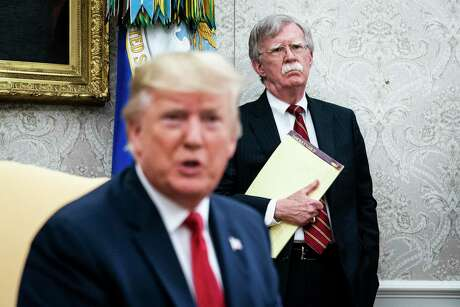 John Bolton listens to President Donald Trump in the White House in July 2019.